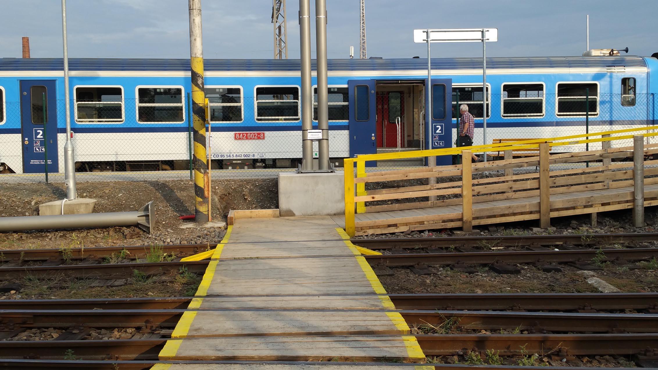 Příchod na 1.nástupiště přes koleje, po dřevěném přechodu.