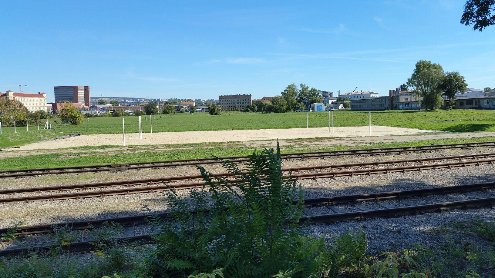 Pohled z cyklostezky u řeky Svratky na Dolní nádraží, na louce již rostou první sportoviště.